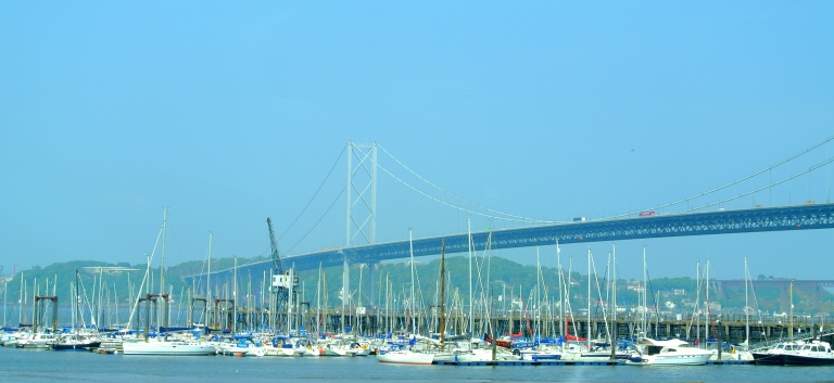 Sailboats docked in front of Forth Road Bridge.