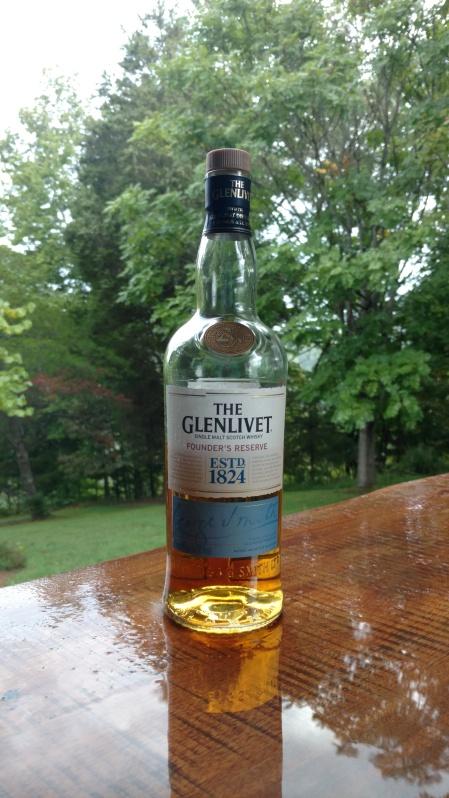 A bottle of The Glenlivet sitting on an outside bar in the rain.