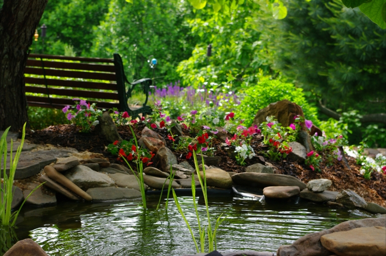 A garden bench and pink and red petunias next to a small pond.
