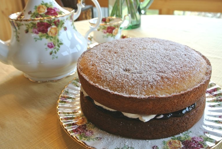A Victoria Sponge on a pretty plate next to a matching teapot.