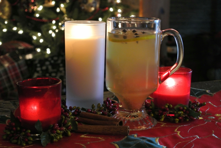 Hot Toddy and candles on a table decorated for Christmas.
