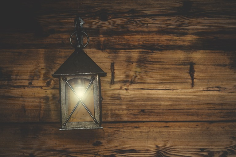 A lantern hanging on a wood paneled wall.