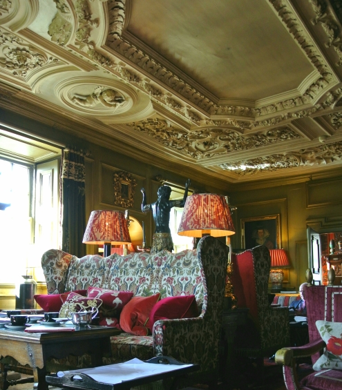 Ornate carved ceiling and a sofa with a bold floral print.