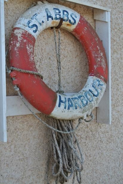 A life tube that says 'St. Abbs Harbor.'