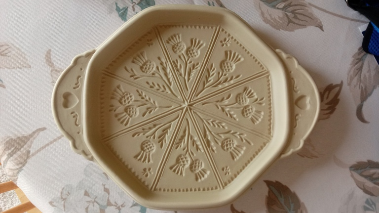 A ceramic thistle imprinted shortbread pan.