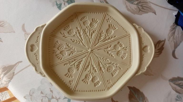A ceramic thistle imprinted shortbread pan.