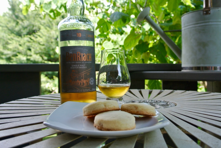 A bottle of Ben Riach, a glass of whisky, and three shortbread cookies on a plate.