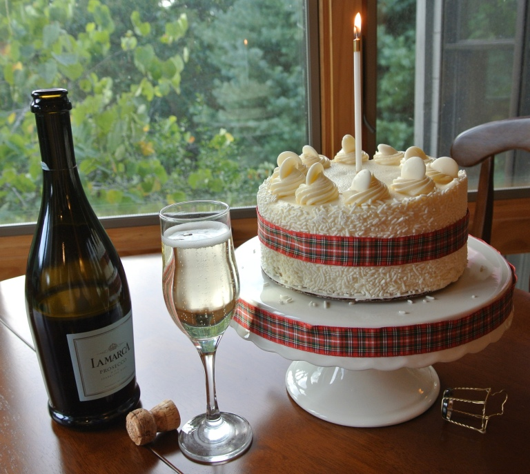 A decorative cake with a plaid ribbon and a candle next to a bottle and glass of champagne.