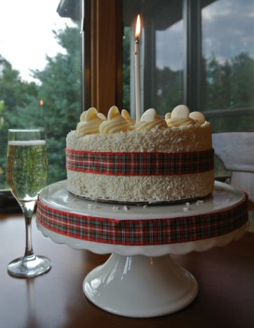 A cake with a plaid ribbon and a candle next to a glass of champagne.