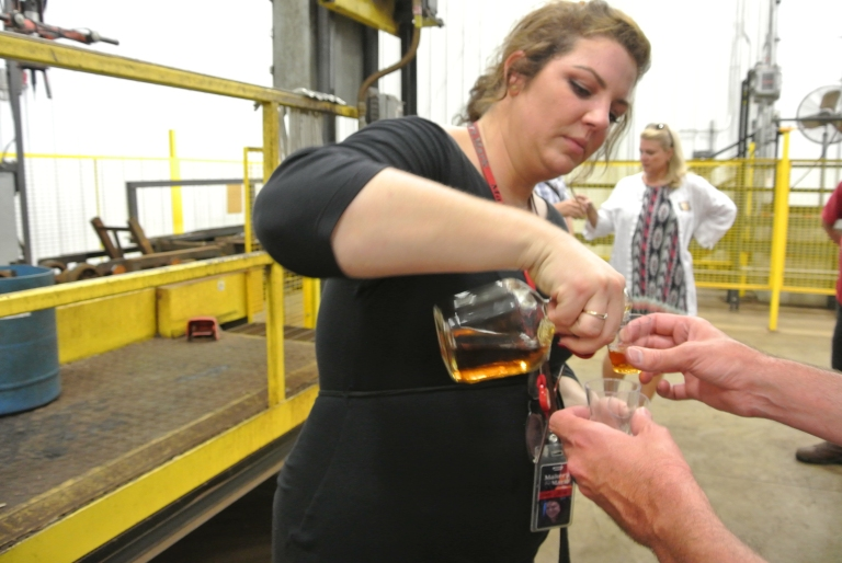 A woman pouring whiskey into a glass.